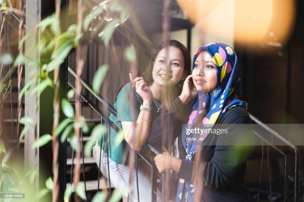 Zwei junge weibliche Arbeitskollegen sprechen während der Bremse. : Stock-Foto