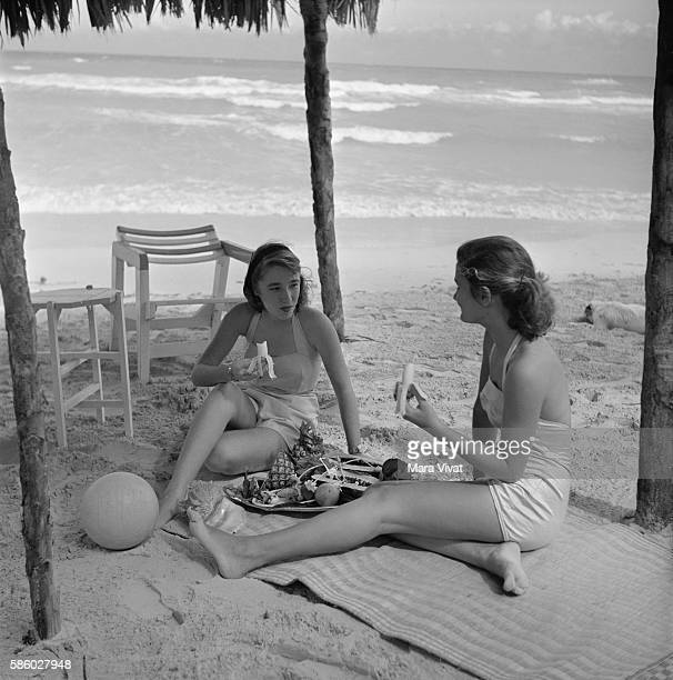 Two Young Females at Beach Eating Bananas