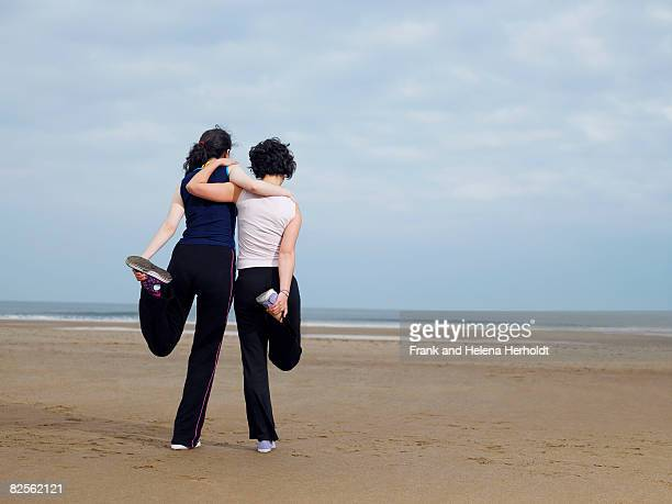 Two young females stretching on beach