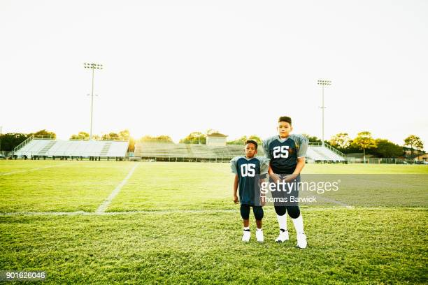 Two young football teammates standing together on field after football game