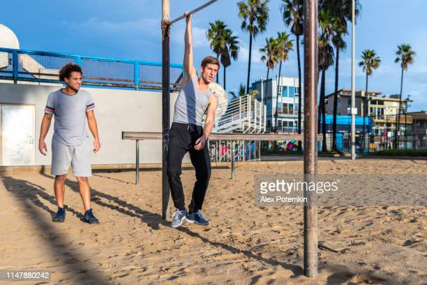 two young friends doing pull-up exercises on the chin-up bar - alex potemkin or krakozawr latino fitness stock photos and pictures