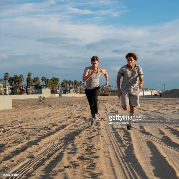 two young friends jogging at the beach - alex potemkin or krakozawr latino fitness stock photos and pictures
