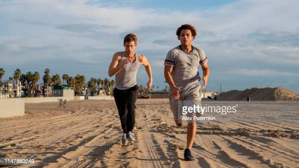Two young friends jogging at the beach