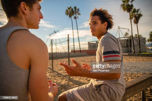 two young friends, latino and caucasian-white, sitting and resting at the muscle beach outdoor sporting area after the fitness exercise. - alex potemkin or krakozawr latino fitness stock photos and pictures