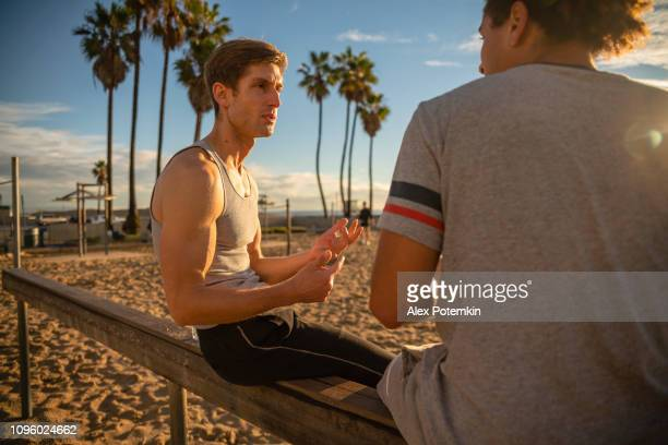 Two young friends, Latino and Caucasian-White, sitting and resting at the Muscle Beach outdoor sporting area after the fitness exercise.