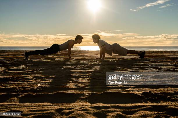 two young friends, latinx and caucasian white men, doing fitness push-up workout on the beach at sunset. - alex potemkin or krakozawr latino fitness stock photos and pictures
