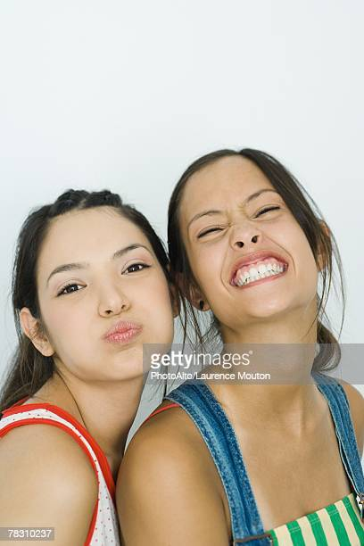 Two young friends making faces at camera, portrait