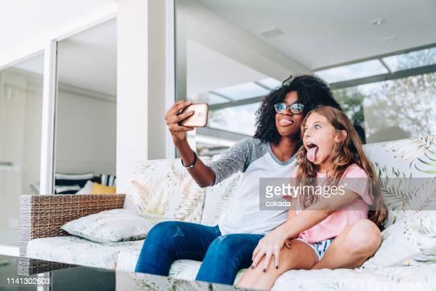 dois amigos novos que fazem as faces engraçadas ao tomar um selfie - dama de companhia - fotografias e filmes do acervo