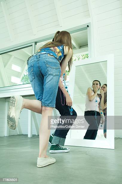 two young friends standing, looking in mirror, one whispering in the other's ear, the other covering mouth - bending over stock pictures, royalty-free photos & images