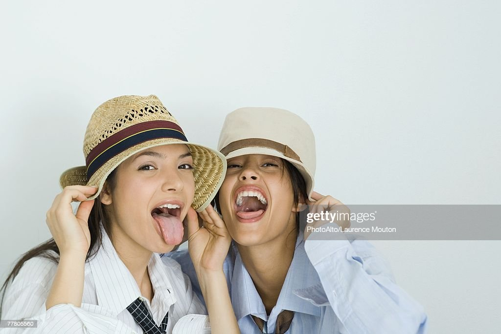 Two young friends wearing hats, sticking out tongues, looking at camera, portrait : Stock Photo