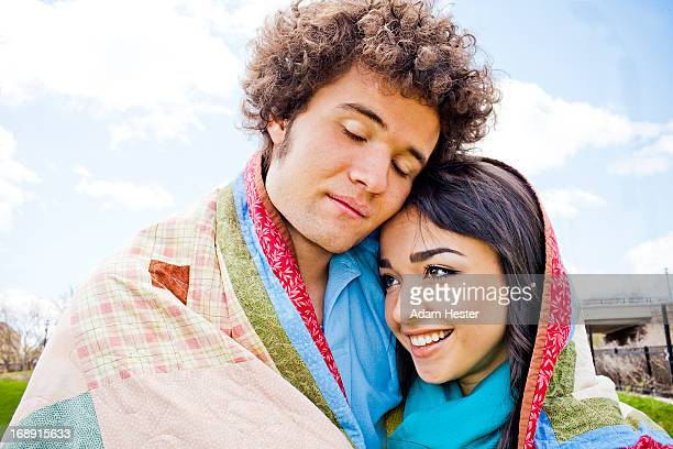 Two young friends wrapped in a quilt together.