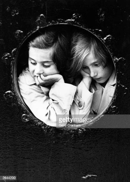 Two young GermanJewish refugees at the porthole of the liner 'St Louis' finally arrive at Antwerp after being refused entry to Cuba and Miami prior...