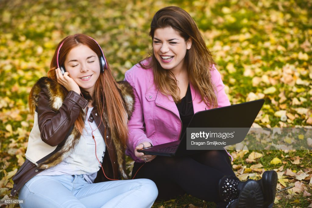 Two young girl sitting in a park and listening music : Stock Photo