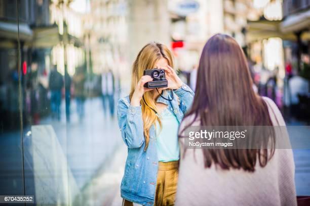 Two young girlfriends, having fun, photographing, outdoors. Shallow DOF. Belgrade, Serbia, Europe