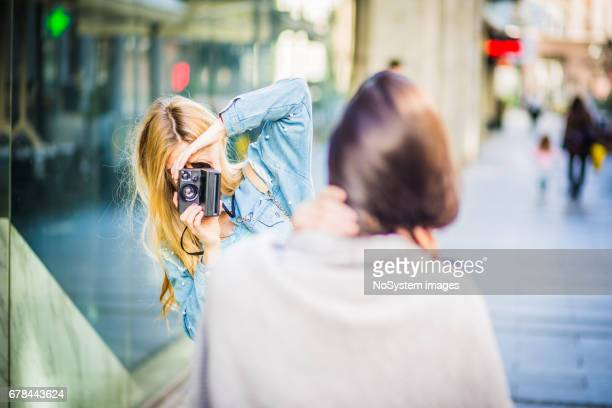 Two young girlfriends, having fun, photographing, outdoors. Shallow DOF
