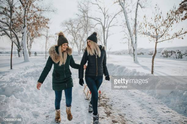 two young girls are having fun in the snow and winter games. - winter coat stock pictures, royalty-free photos & images