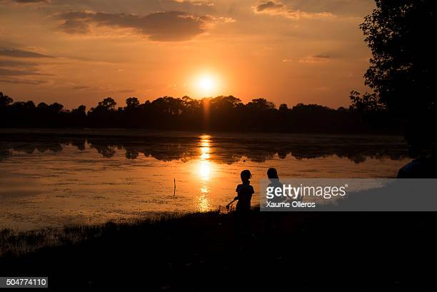 Two young girls are silhouetted in front of a lake near Angkor Wat on January 1 2016 in Siem Riep Cambodia Angkor was the capital city of Khmer...
