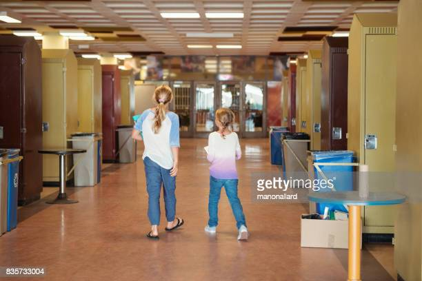 Two young girls back to school walking in the school near the lockers.