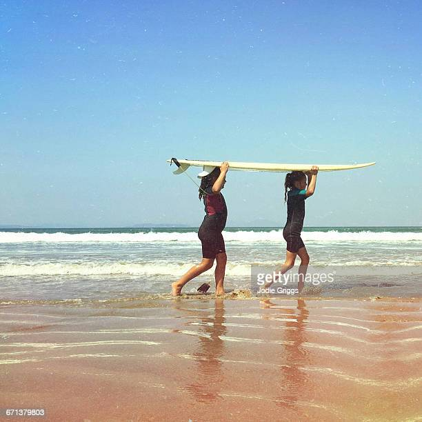 Two young girls carrying a surfboard together