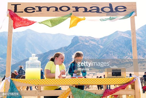 Two young girls counting money at their lemonade stand