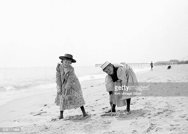 Two young girls dig in the beach sand ca 1905