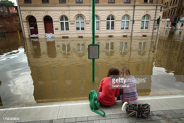 Two young girls discuss apps on their smartphones while sitting in a street flooded by the nearby Elbe river in the historic city center on June 6...