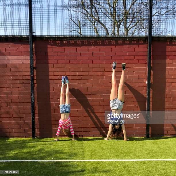 two young girls doing a handstand together - taken on mobile device stock photos and pictures