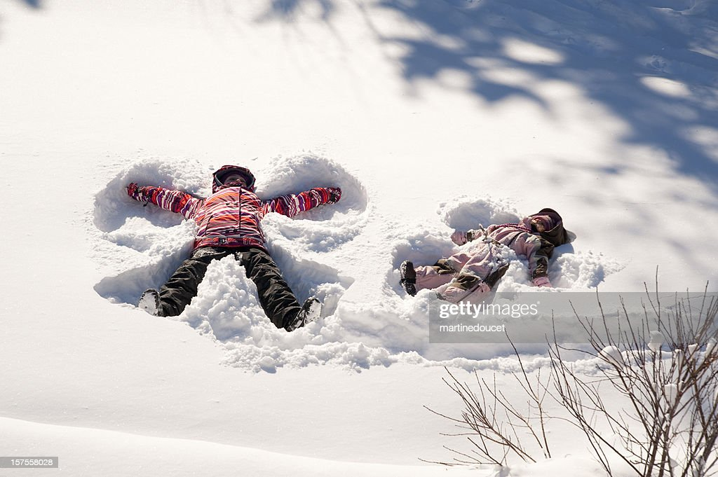Two young girls doing snow angels, full length horizontal. : Stock Photo