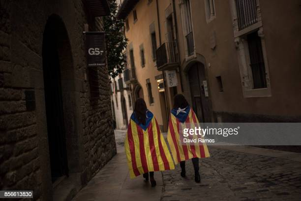 Two young girls draped in a Catalan proindependence flag walk down a street of the old town after a protest against the violence that marred...