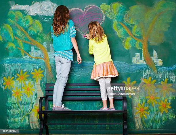Two young girls drawing a heart on a park bench.
