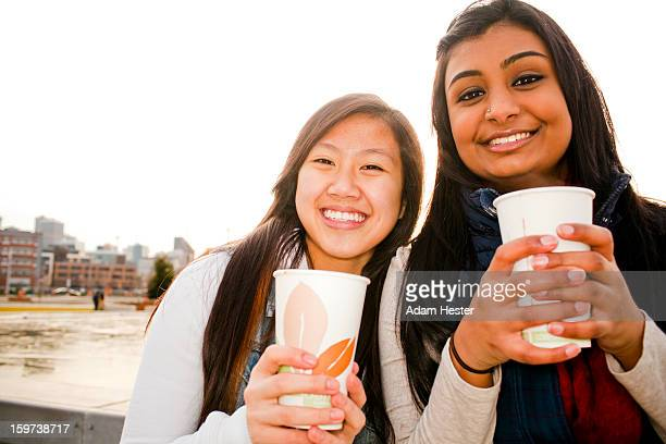 Two young girls drinking a hot beverage outside.