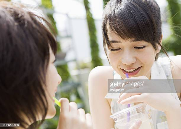 Two young girls drinking juice
