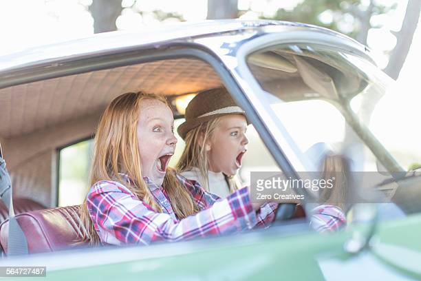 two young girls driving car, looking scared - wrong way stock pictures, royalty-free photos & images