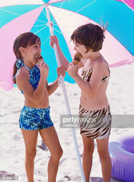 two young girls eating ice-cream holding umbrella - only girls stock pictures, royalty-free photos & images