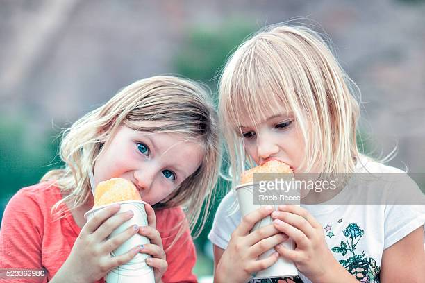 two young girls (4-7) eating snow cones together - robb reece stock pictures, royalty-free photos & images