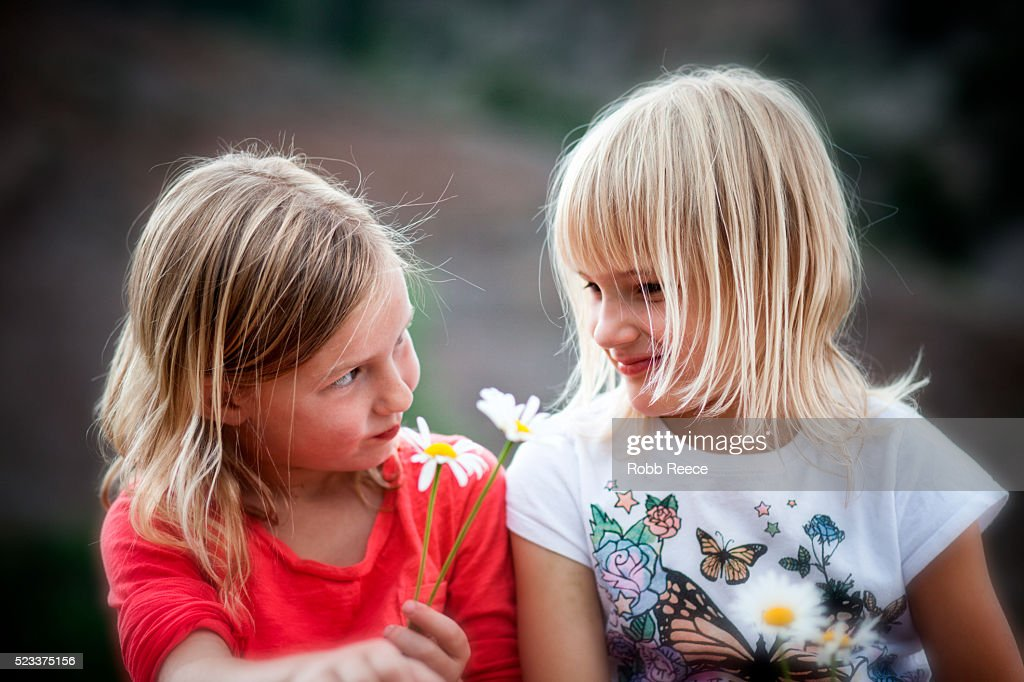 Two young girls (6-9) giving each other flowers : Stock Photo
