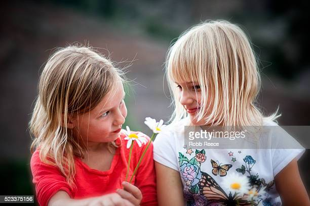 two young girls (6-9) giving each other flowers - robb reece stock-fotos und bilder