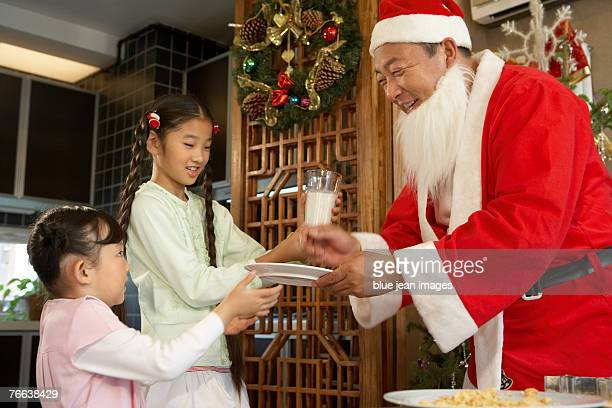 Two young girls giving milk and cookies to Santa Claus.