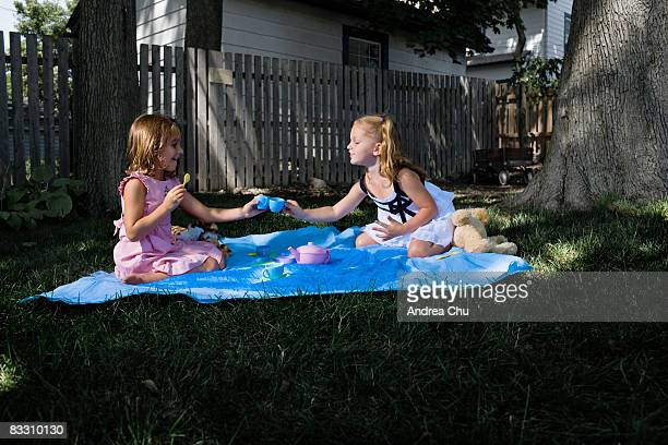 Two young girls having a outdoor tea party.