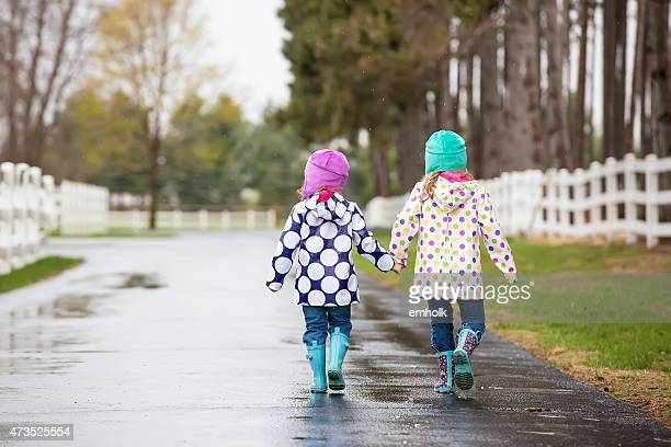 two young girls holding hands walking in rain - raincoat stock photos and pictures