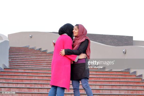 two young girls in hijab (head scarf) meeting together in a happy mood - punjabi girls images stock photos and pictures