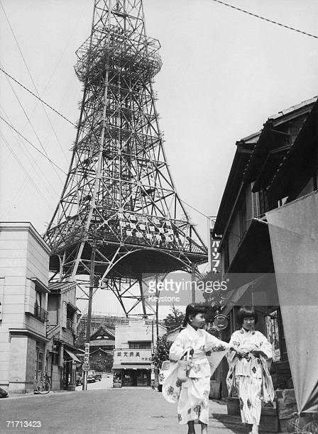 Two young girls in Kimonos in a street near the almost completed Tokyo Tower July 1958 The tower is a TV and radio broadcasting antenna as well as a...