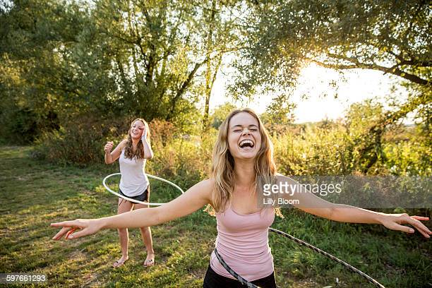 two young girls in rural environment, fooling around, using hula hoops, - showing off stock pictures, royalty-free photos & images