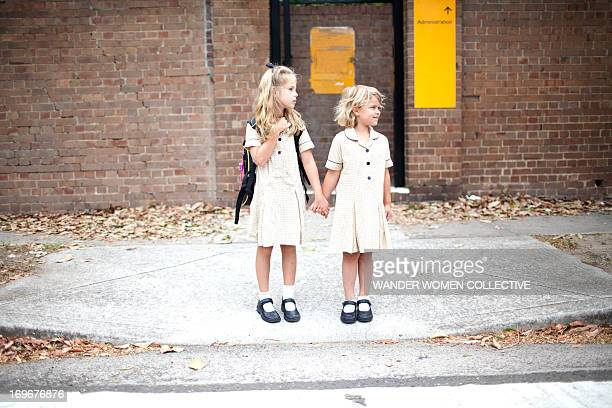two young girls in school uniform crossing road - schuluniform stock-fotos und bilder
