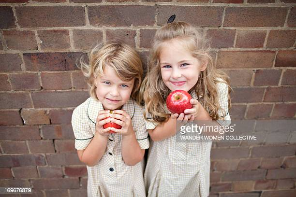 Two young girls in school uniform eating apples