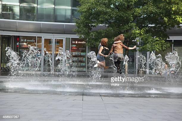 2 つの若い女の子をジャンプの噴水 - 人の背中 ストックフォトと画像