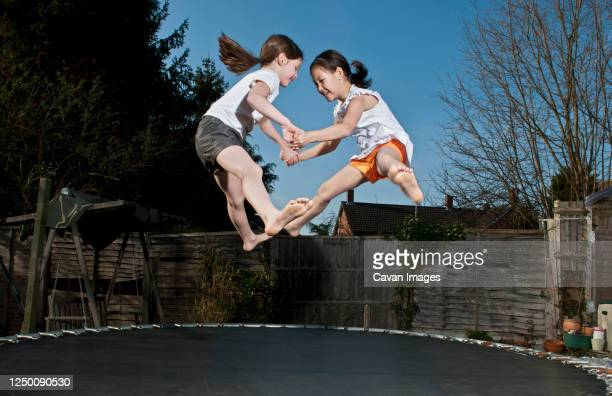 two young girls jumping on trampoline in woking - england - individual event stock pictures, royalty-free photos & images