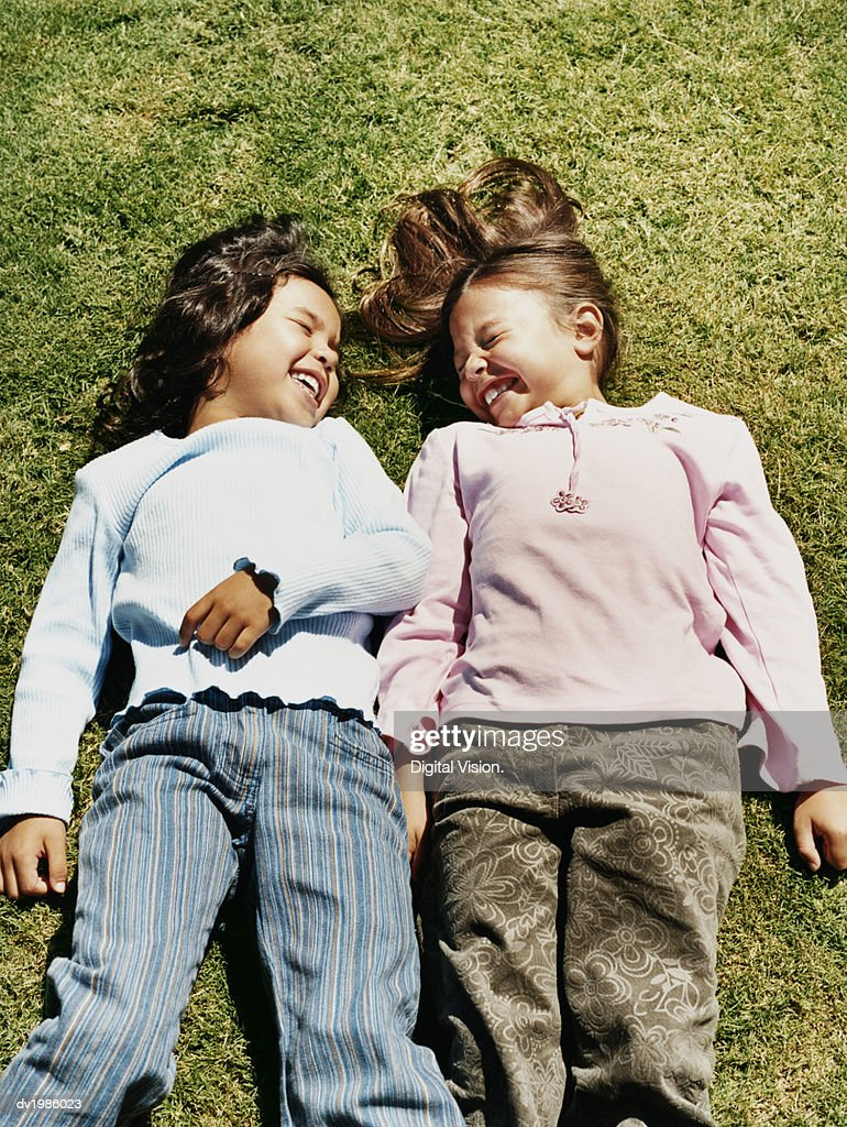 Two Young Girls Laughing Together on the Grass : Stock Photo