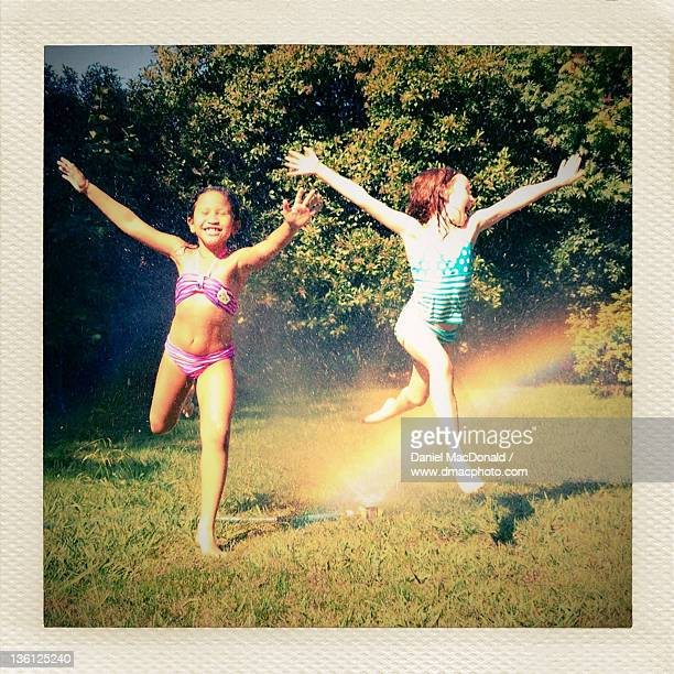 Two young girls leaping through sprinkler