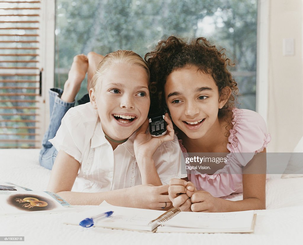 Two Young Girls Lie Side by Side on a Bed, Listening to a Mobile Phone and Smiling : Stock Photo